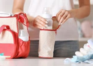 photo of mom packing diaper bag with baby bottle