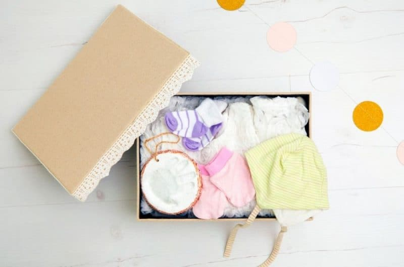box of baby items, including clothes and handprint ornament