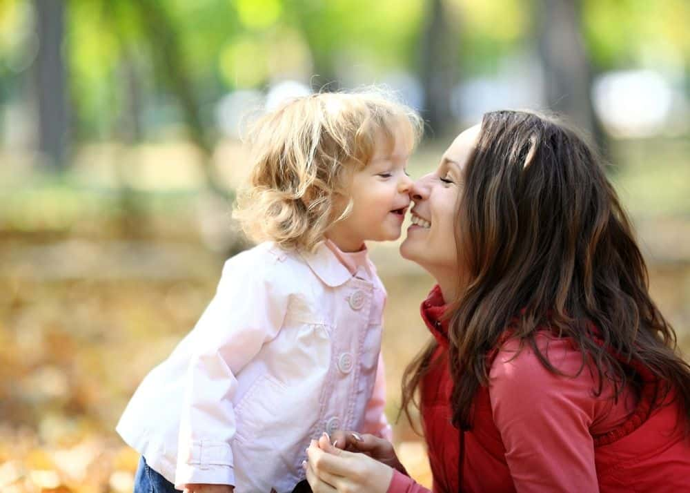 little girl kissing aunt touching noses