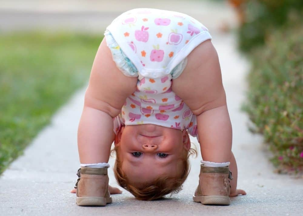 toddler girl bending over looking through legs in downward dog pose