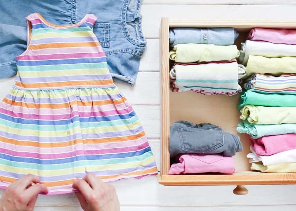 person folding clothes for a toddler girl's capsule wardrobe