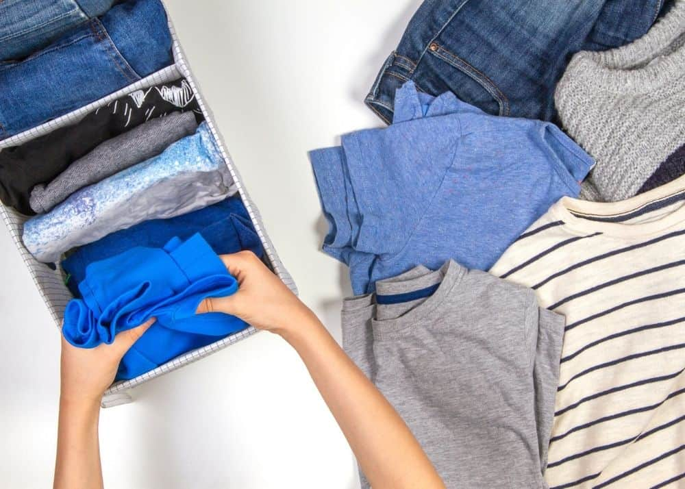 person folding clothes for a toddler boy's capsule wardrobe