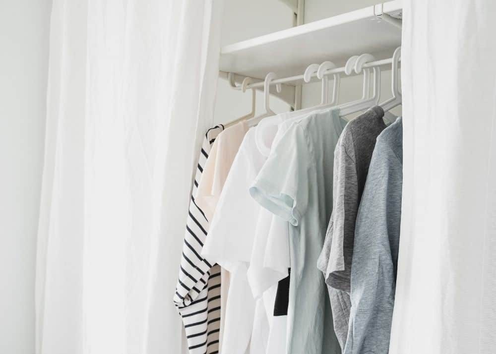capsule wardrobe for toddlers with basic tops on hangers in closet