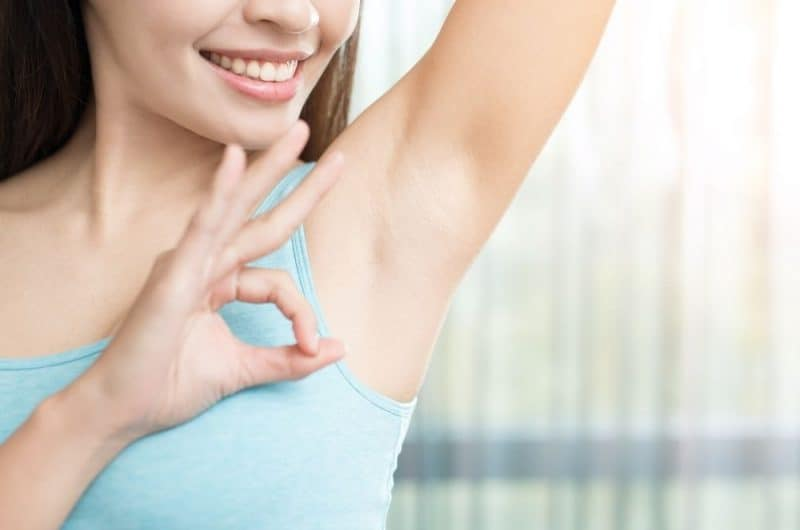 woman giving the okay sign after getting rid of postpartum body odor