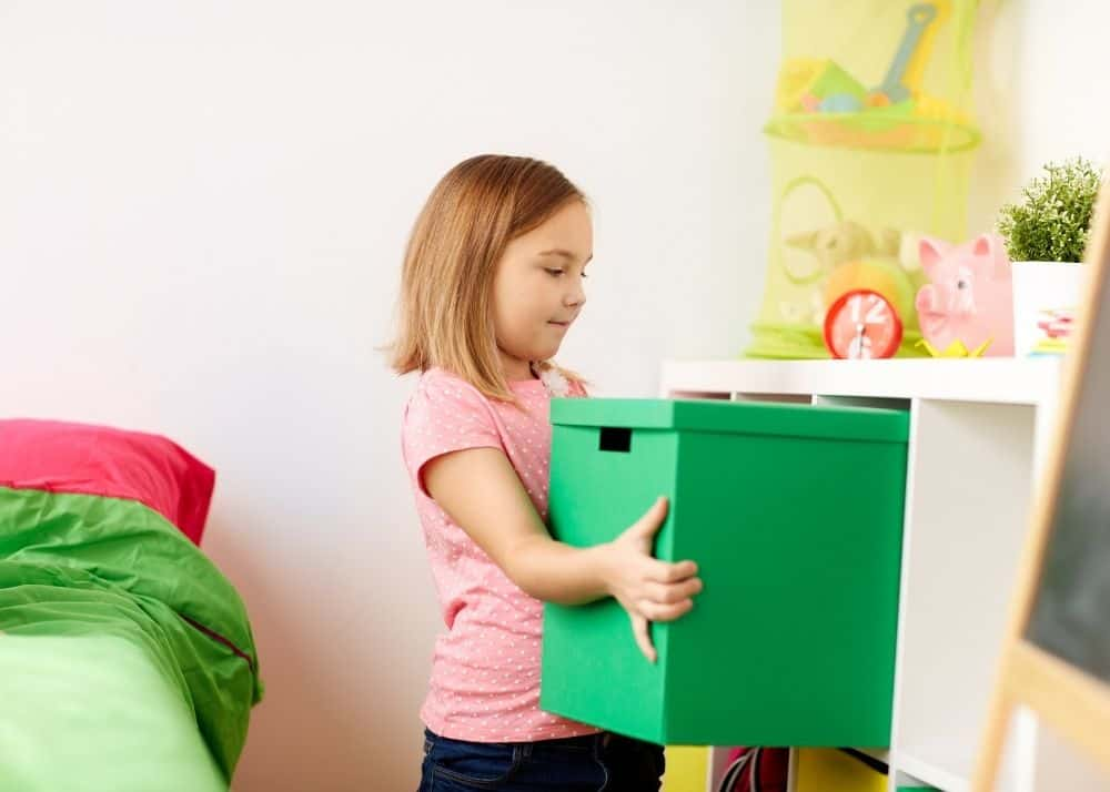 little girl putting bin of toys back on book shelf for toy rotation