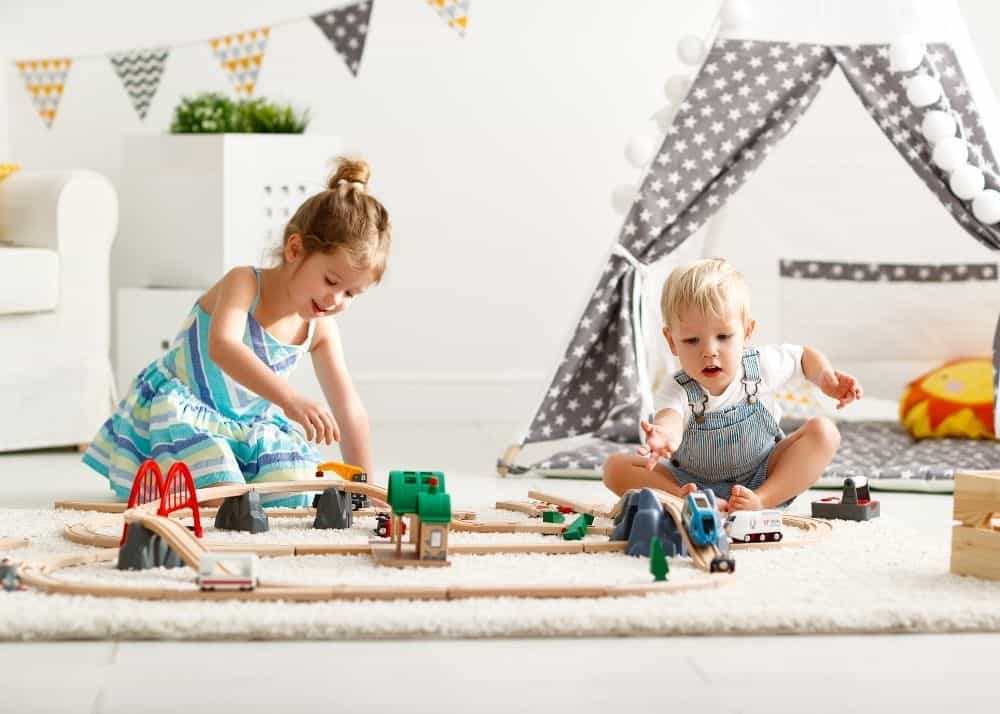 older sister and little brother playing with train set on floor in front of tent for toy rotation