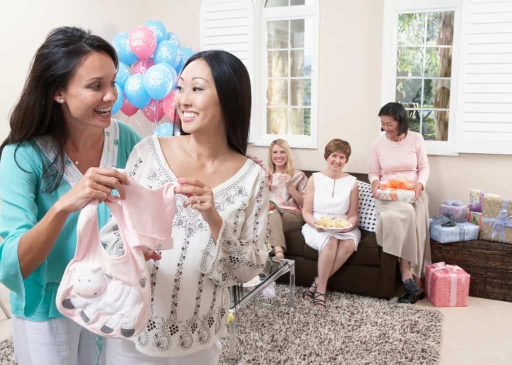 women at a display baby shower fawning over cute clothes