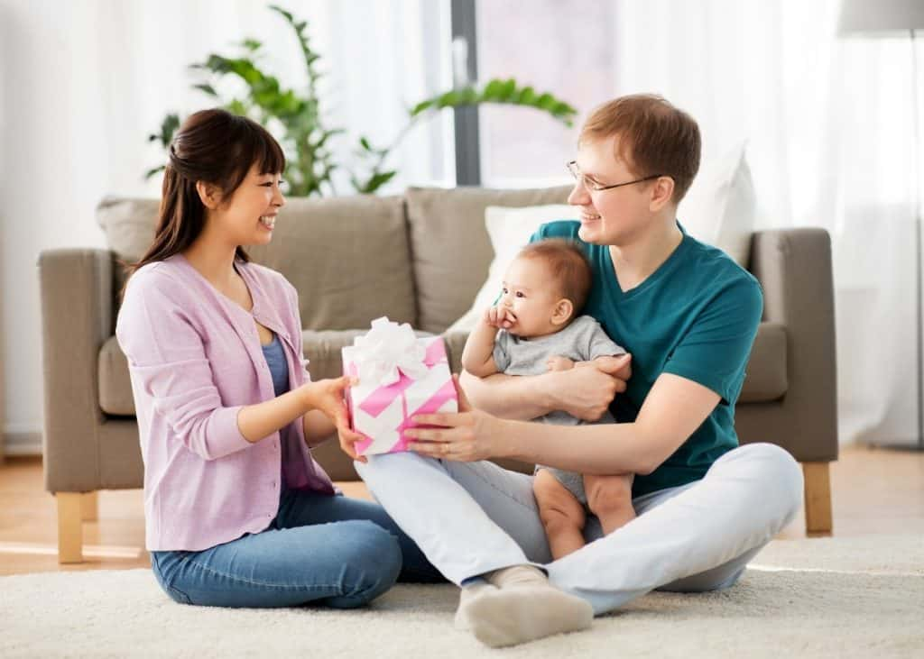 new father giving new mother push present with baby in lap