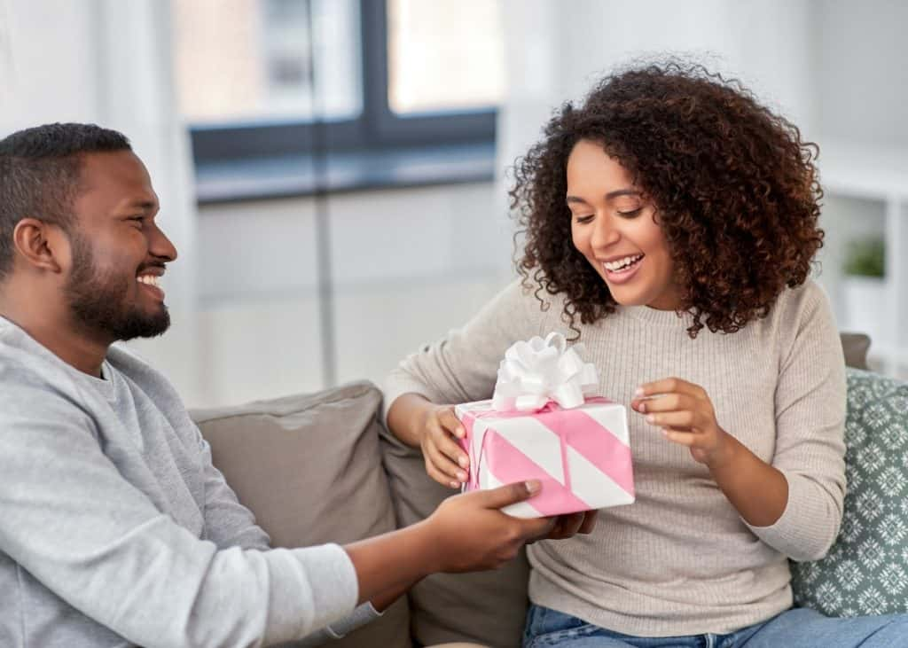 happy new dad giving happy new mom wrapped push present